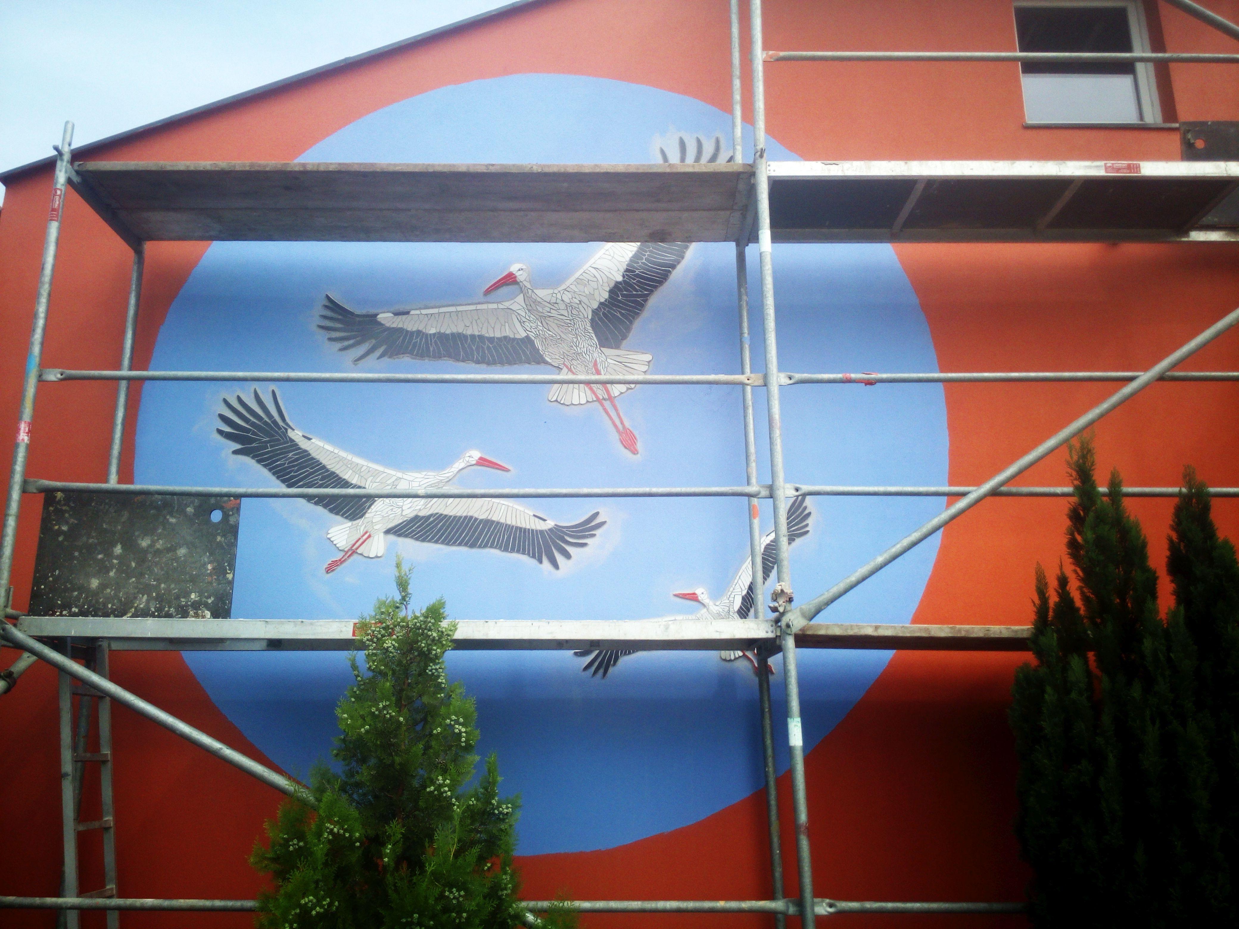 trzy mozaikowe bociany na elewacji szkoły w Ciecierzycach, wersja z rusztowaniem